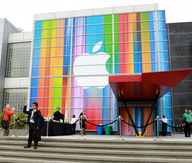 apple-fans-posing-in-front-of-logo
